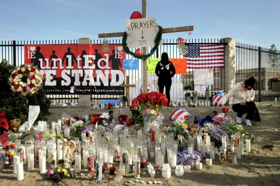 Laura Muela (far right) waters the flowers at a makeshift memorial honoring the 14 people shot to death San Bernardino, Calif. The female killer has become a focus of the terrorism investigation. Photo: Jae C. Hong /Associated Press / AP