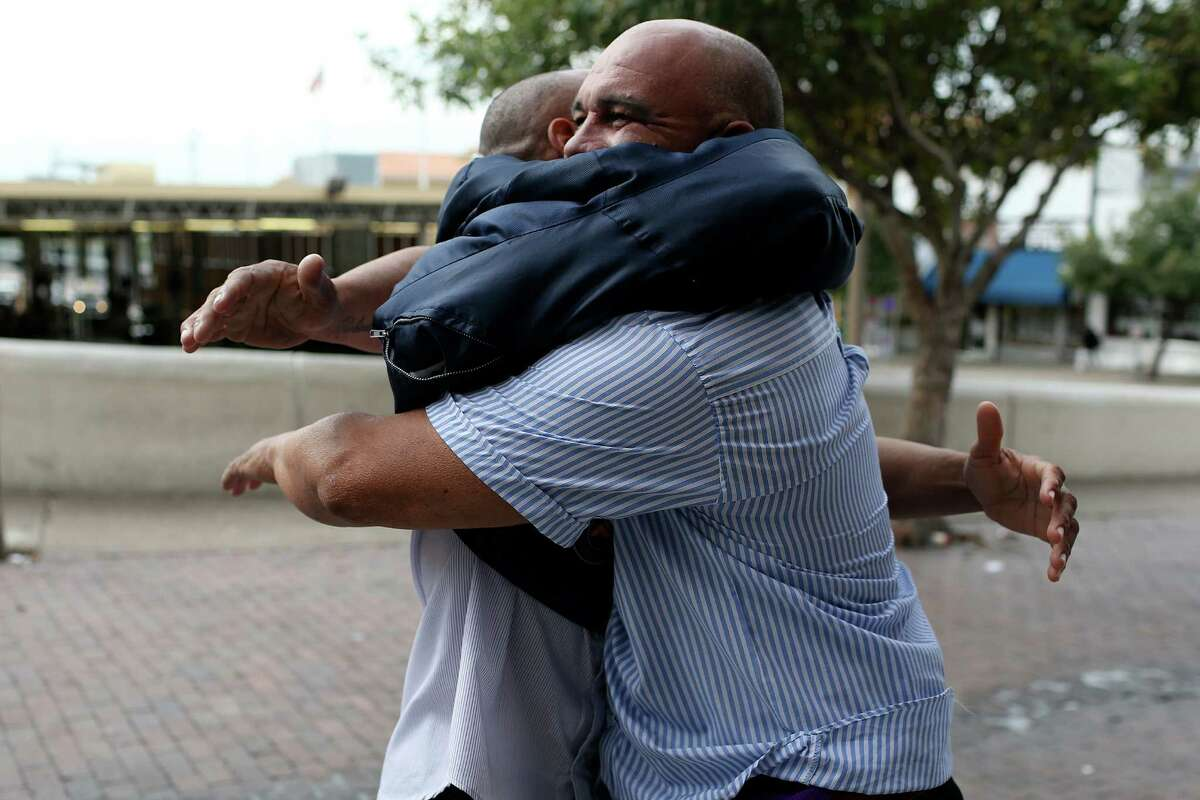 Michel Castaneda, 29, left, and Roberto Mendoza, 47, hug after reuniting upon their release from the U.S. Port of Entry at Laredo.