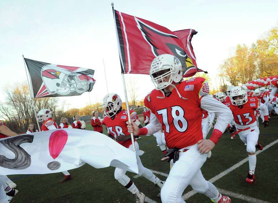 Alex Buftone leads Greenwich onto the field before last month's home game against Ridgefield. The Cardinals played the toughest schedule in the FCIAC this season based on the winning percentage of their opponents. Photo: Bob Luckey Jr. / Hearst Connecticut Media / Greenwich Time