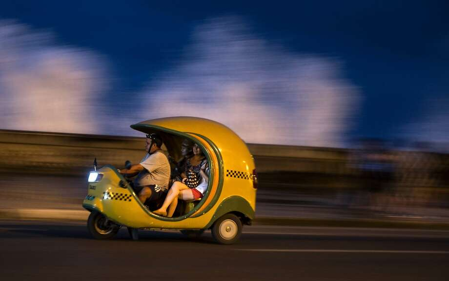 """Tourists travel in a """"Coco taxi"""" along the Malecon as waves break above the sea wall in Havana, Cuba, Saturday, Dec. 5, 2015. Coco taxis are one of many kinds of taxis in the capital fashioned out of motorcycles, popular with both tourists and locals. Photo: Ramon Espinosa, Associated Press"""