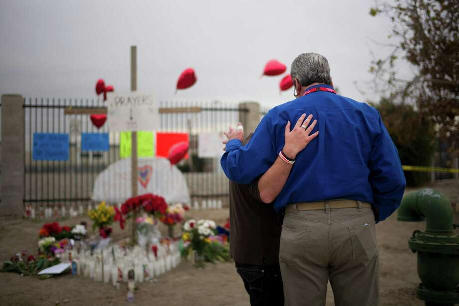 Chaplain Chuck Bender, right, prays with Michael Davila at a makeshift memorial honoring the victims of Wednesday's shooting rampage, Friday, Dec. 4, 2015, in San Bernardino, Calif. The FBI said Friday it is officially investigating the mass shooting in California as an act of terrorism, while a U.S. law enforcement official said the woman who carried out the attack with her husband had pledged allegiance to the Islamic State group and its leader on Facebook. (AP Photo/Jae C. Hong) Photo: Jae C. Hong, STF / AP