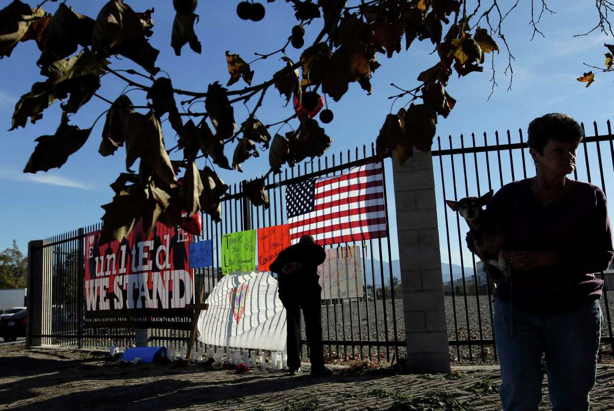 Libing Chen, left, and Betty Borda pay their respects at a makeshift memorial on Saturday, Dec. 5, 2015, in San Bernardino, Calif. A husband and wife on Wednesday, dressed for battle and carrying assault rifles and handguns, opened fire on a holiday banquet for his co-workers, killing multiple people and seriously wounding others in a precision assault, authorities said. Hours later, the couple died in a shootout with police. (AP Photo/Chris Carlson)