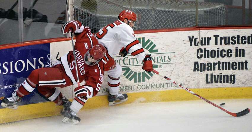 RPI's #25 Drew Melanson, right, comes up with the puck after a collision with Harvard's #5 Clay Anderson during Saturday's game at the Houston Field House Dec. 5, 2015 in Troy, NY. (John Carl D'Annibale / Times Union)