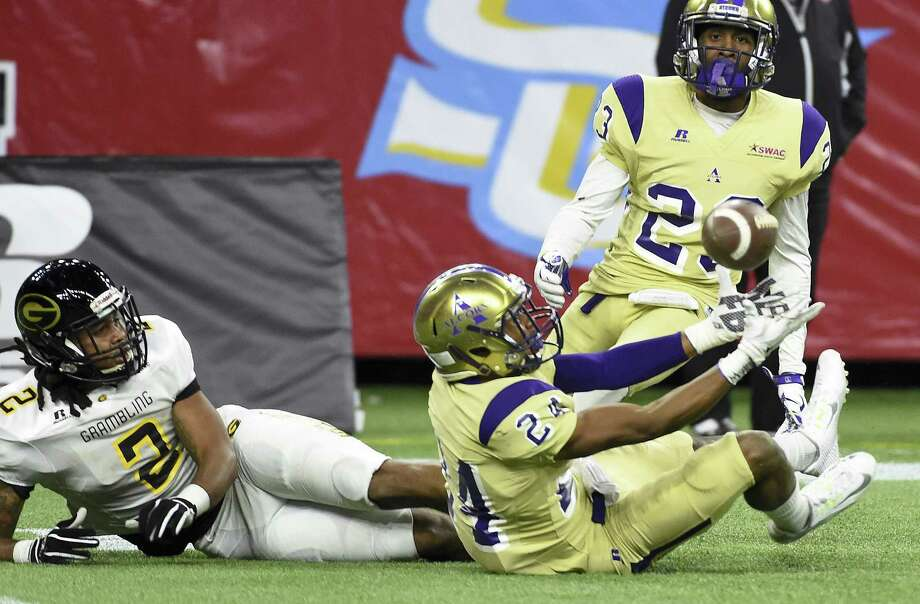 Sitting down on the job pays off for Alcorn State defensive back Warren Gatewood, right, as he intercepts a pass intended for Grambling's Verlon Hunter in the third quarter. Gatewood finished with three interceptions. Photo: Eric Christian Smith, FRE / FR171023 AP