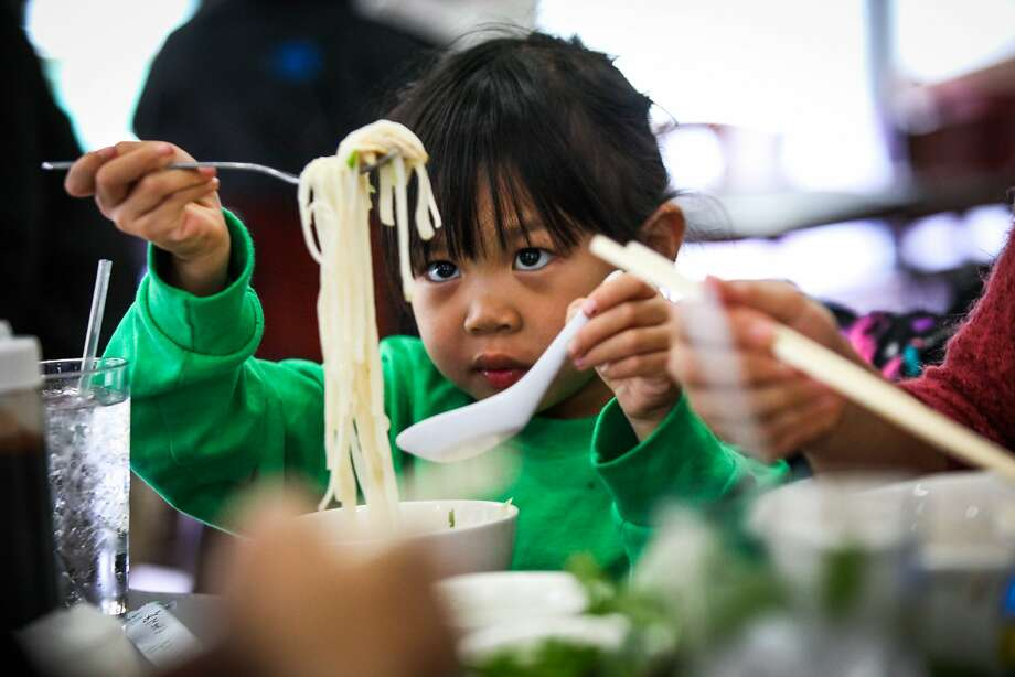 Raina To, 6, eats a bowl of noodles with her family at Ha Nam Ninh restaurant in San Francisco, California on Saturday, December 5, 2015. Photo: Gabrielle Lurie, Special To The Chronicle
