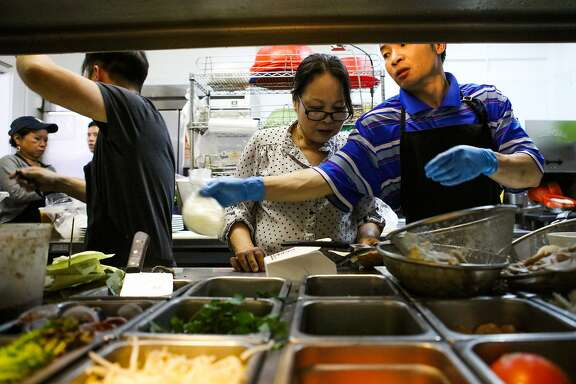 Muoi Au (center) talks to her sons, Dzoung Nguyen (left) and Son Nguyen (right), as they prepare Vietnamese dishes in kitchen of Ha Nam Ninh restaurant in San Francisco, California on Saturday, December 5, 2015.