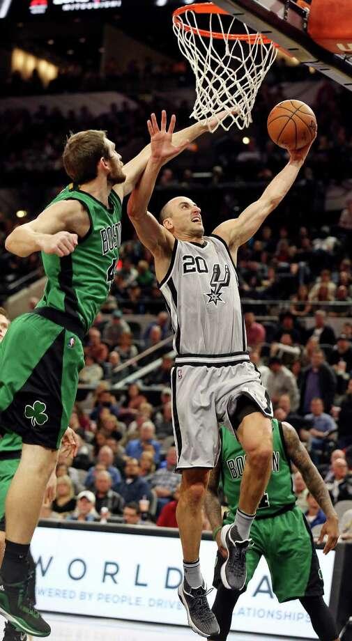 San Antonio Spurs' Manu Ginobili drives to the basket around Boston Celtics' Tyler Zeller during first half action Saturday Dec. 5, 2015 at the AT&T Center. Photo: Edward A. Ornelas, Staff / San Antonio Express-News / © 2015 San Antonio Express-News