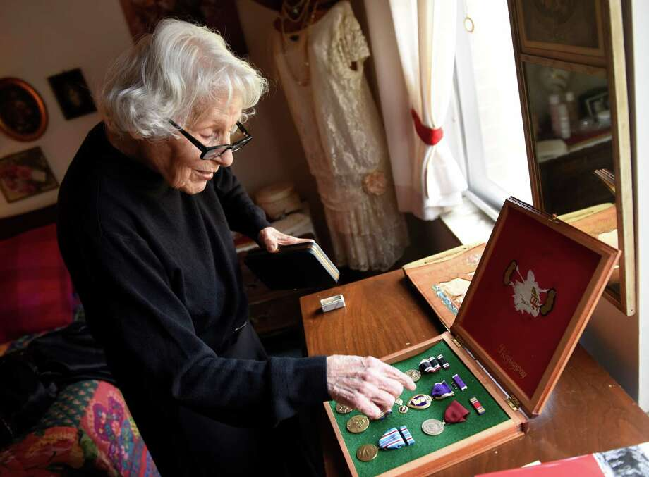 """Catherine Quoma shows World War II medals belonging to her brother, Ferdinand """"Freddie"""" Meringolo, at her home in Greenwich, Conn. Thursday, Dec. 3, 2015. Meringolo, a Navy sailor, was captured in the Philippines and later killed by the Japanese after he attempted an escape in 1943. Photo: Tyler Sizemore / Hearst Connecticut Media / Greenwich Time"""