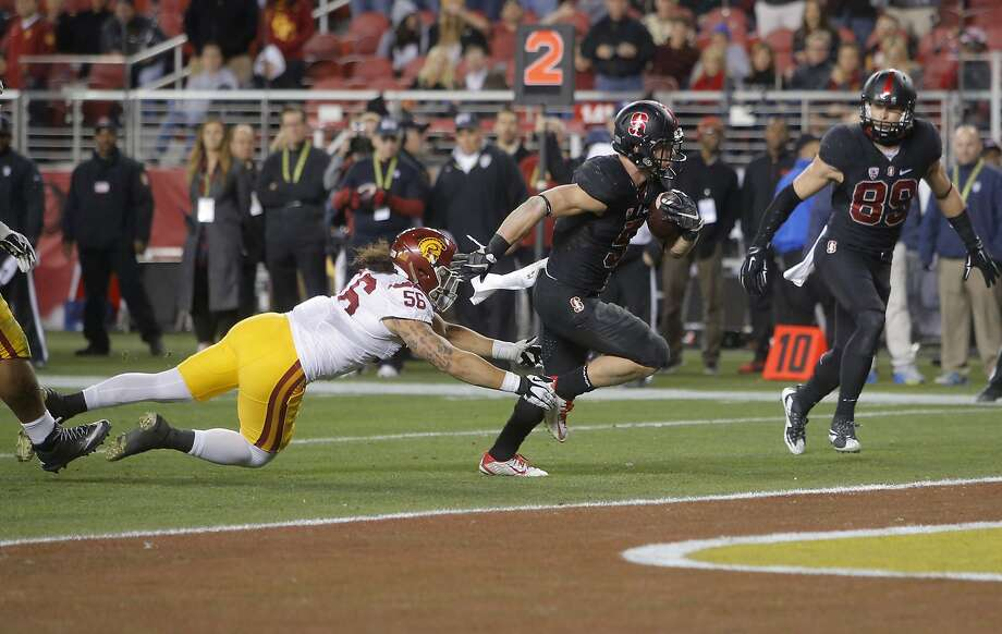 Stanford's Christian McCaffrey, 8 escapes from USC's Wesley Annan, 56 for a fourth quarter touchdown, as Stanford went on to beat on the USC Trojans 41-22 in the NCAA College PAC-12 Football Championship at Levi Stadium in Santa Clara, Calif., on Saturday December 5, 2015. Photo: Michael Macor, The Chronicle