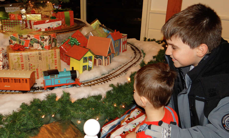 Sam Smith and younger brother Cameron, of Fairfield, watch G-Scale trains whiz by on the opening night of the Holiday Express Train Show at Fairfield Museum and History Center. Photo: Mike Lauterborn / For Hearst Connecticut Media / Fairfield Citizen
