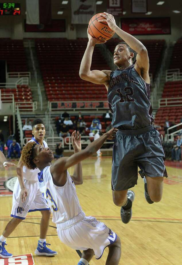 Central's Tyrin Atwood shoots over the blocking efforts of Ozen's Derrian Jones during Saturday's YMBL boy's finals game at the Montagne Center.  Photo taken Saturday, December 05, 2015  Kim Brent/The Enterprise Photo: Kim Brent / Beaumont Enterprise