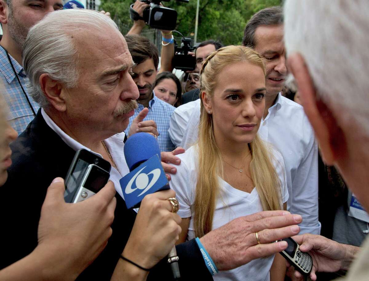 Lilian Tintori, the wife of jailed opposition leader Leopoldo Lopez, center, arrives to a polling station with Colombia's former President Andres Pastrana, left, and Bolivia's former President Jorge Quiroga, as they speak with a member of the National Electoral Council during congressional elections in Caracas, Venezuela, Sunday, Dec. 6, 2015. Polls show the opposition coalition holding a 30 point lead.