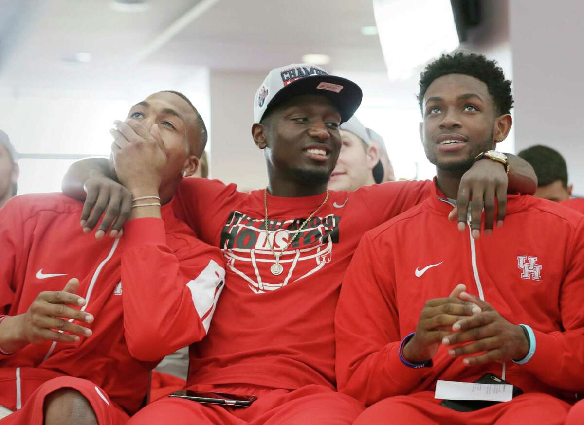 Chance Allen, wide receiver (21), from left, DeMarcus Ayers, wide receiver (10), and Greg Ward, Jr., quarterback (1), celebrate as Houston's bowl schedule is announced during a bowl-selection watch party in the TDECU Stadium club Sunday, Dec. 6, 2015, in Houston. Houston will play Florida State in the Chick-fil-A Peach Bowl on Dec. 31.
