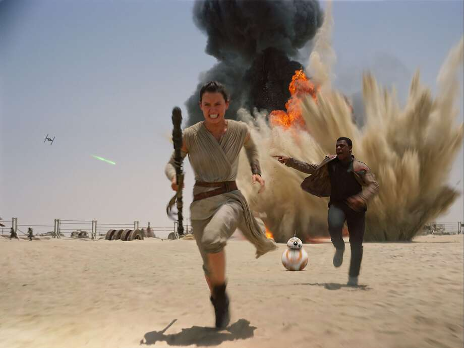 """Daisy Ridley (Rey) and John Boyega (Finn) try to elude forces from the former Empire in """"Star Wars:  The Force Awakens."""" Photo: Associated Press"""