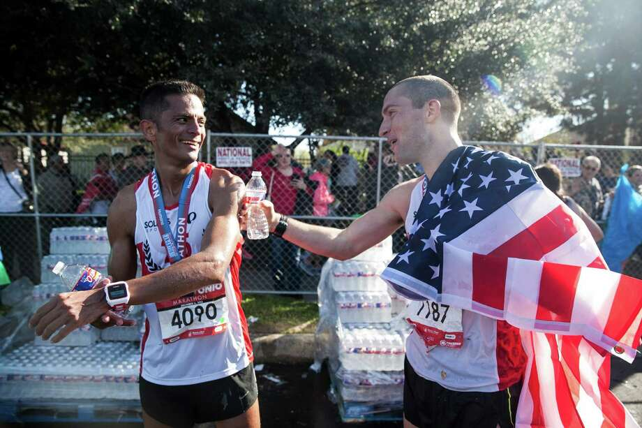 Mark Greene congratulates his friend Ricardo Carrillo, after finishing the full marathon division Sunday Dec. 6, 2015 during the Rock 'n' Roll San Antonio Marathon at the Alamodome. Greene is a San Antonio native and this is his second Rcok 'n' Roll marathon that he has participated in. Photo: Julysa Sosa/ For The San Antonio / San Antonio Express-News / San Antonio Express-News