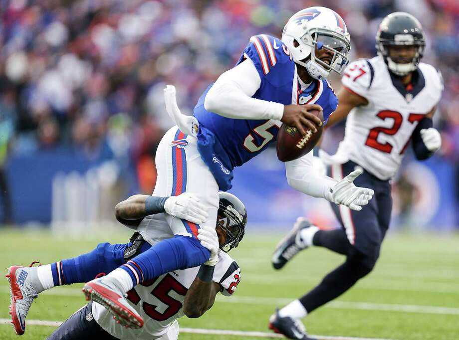 Buffalo Bills quarterback Tyrod Taylor (5) is tackled by Houston Texans cornerback Kareem Jackson (25) as he runs the ball for a 2-yard gain during the third quarter of an NFL football game at Ralph Wilson Stadium on Sunday, Dec. 6, 2015, in Orchard Park, N.Y. Photo: Brett Coomer, Houston Chronicle / © 2015  Houston Chronicle