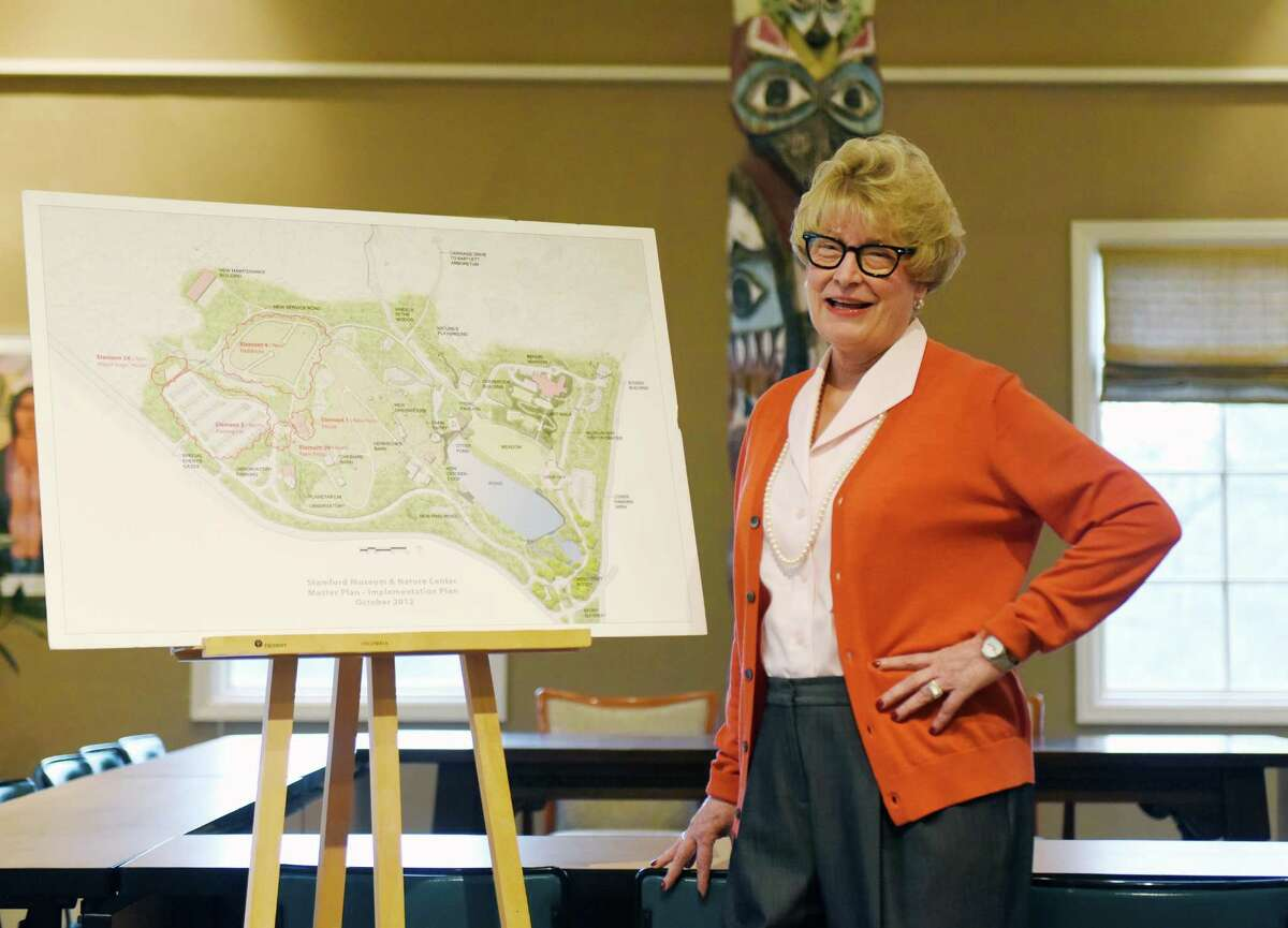 Stamford Museum & Nature Center Executive Director and CEO Melissa Mulrooney poses beside a master site plan of the Museum & Nature Center grounds in Stamford, Conn. Tuesday, Dec. 1, 2015. Mulrooney is marking 10 years as the Museum & Nature Center's executive director and CEO.
