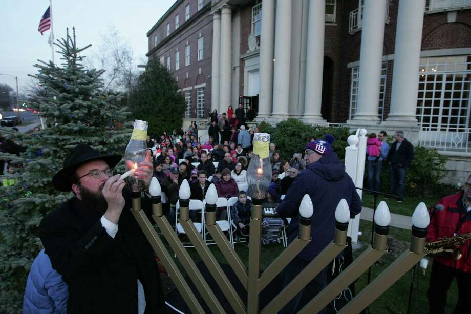 Rabbi Yossi Deren of Chabad Lubavitch of Greenwich lights the first candle of a Menorah during the observance of the First Night of Hanukkah in Greenwich, Conn. on Dec. 6, 2015. Photo: Matthew Brown / For Hearst Connecticut Media / Connecticut Post Freelance