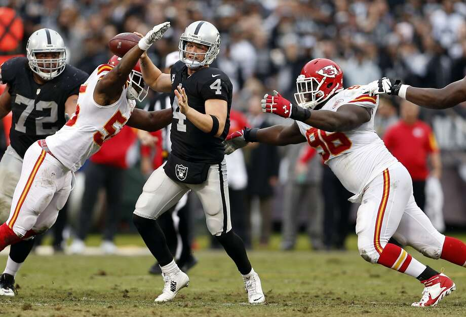Oakland Raiders' Derek Carr is pressured by Kansas City Chiefs' Dee Ford (55) and Jaye Howard causing an interception in 4th quarter of Kansas City's 34-20 win in NFL game at O.co Coliseum in Oakland, Calif., on Sunday, December 6, 2015. Photo: Scott Strazzante, The Chronicle
