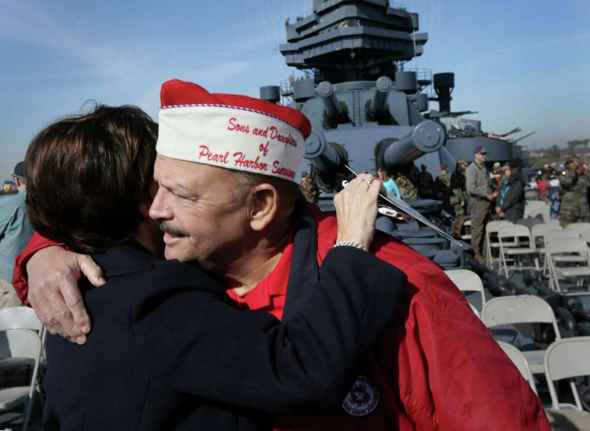 Jeff Smith, right, hugs Jan Roseman during a Pearl Harbor Day ceremony aboard the Battleship Texas Saturday, Dec. 5, 2015, in La Porte. Both are children of Pearl Harbor survivors, and Smith is the past president of the Sons and Daughters of Pearl Harbor Survivors.