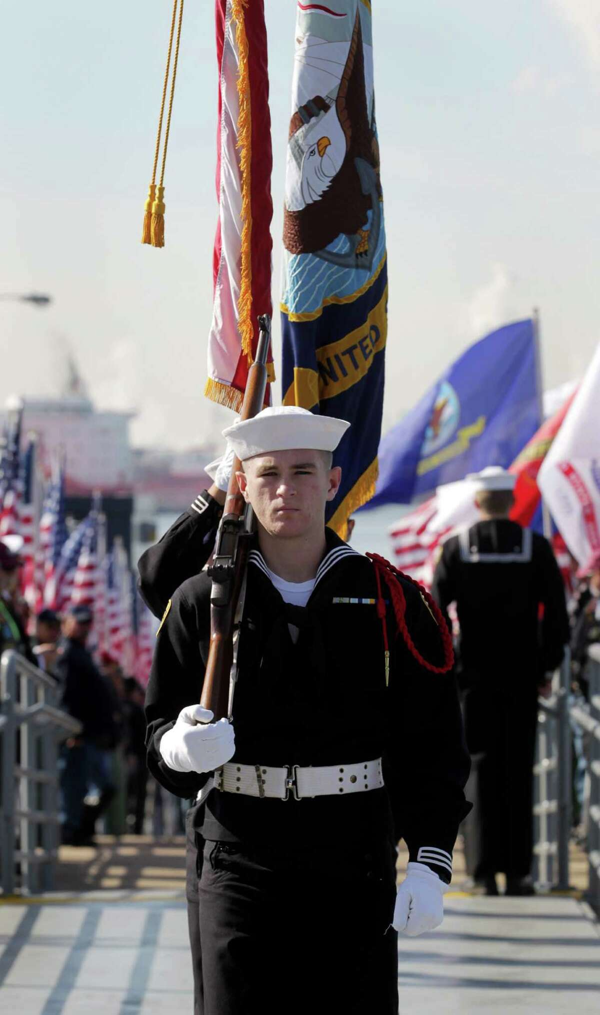 Seaman Benjamin McElyea, a sea cadet, boards the Battleship Texas during a Pearl Harbor Day ceremony Saturday, Dec. 5, 2015, in La Porte.
