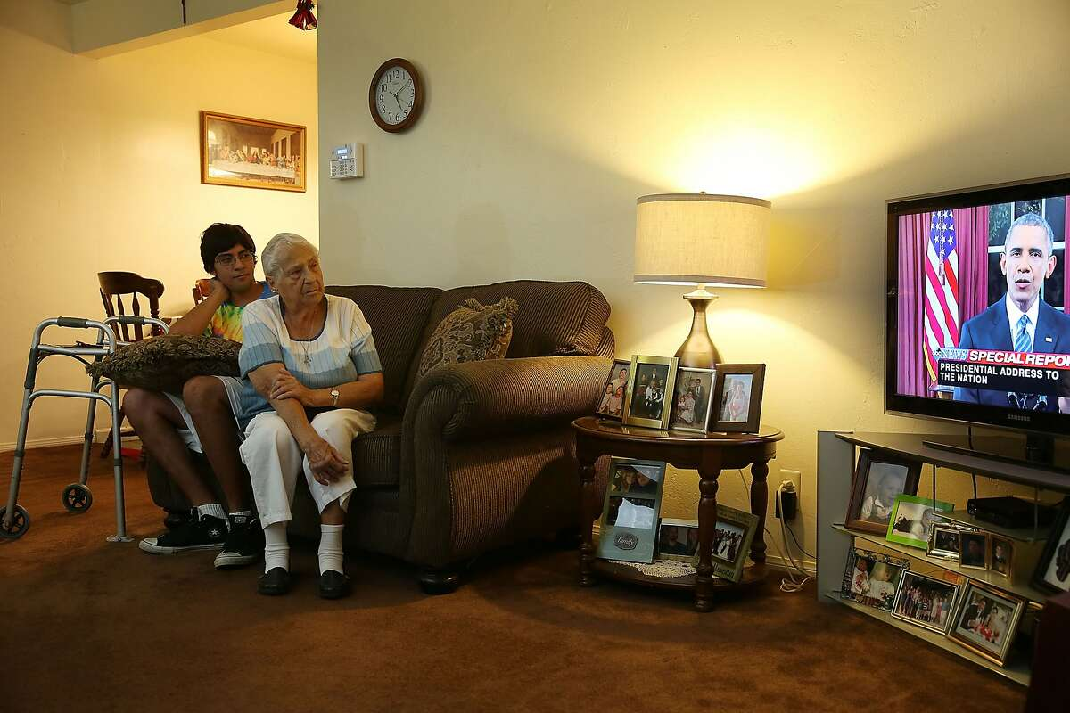 SAN BERNARDINO, CA - DECEMBER 06: Jonathan Tovar sits with his grandmother Helen Medina in her house, which was hit by bullets as police engaged in a gun battle with terror suspects on the street in front, as they watch President Barack Obama give a nationally-televised address from the White House about terrorism following the attack on the Inland Regional Center on December 6, 2015 in San Bernardino, California. Medina hid in her home as the police killed the terror suspects that attacked the Inland Regional Center in San Bernardino that left 14 people dead and another 21 injured on December 2. (Photo by Joe Raedle/Getty Images)