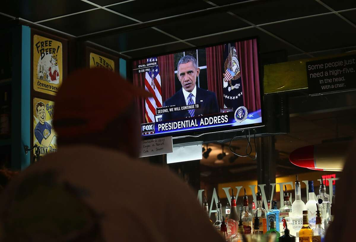 IRVING, TEXAS - DECEMBER 06: Bar patrons watch as President Barack Obama addresses the nation from the Oval Office on December 6, 2015 at the DFW Airport in Irving, Texas. President Obama spoke about the government's campaign against the terrorist threat, following last week's attack in California. (Photo by John Moore/Getty Images)