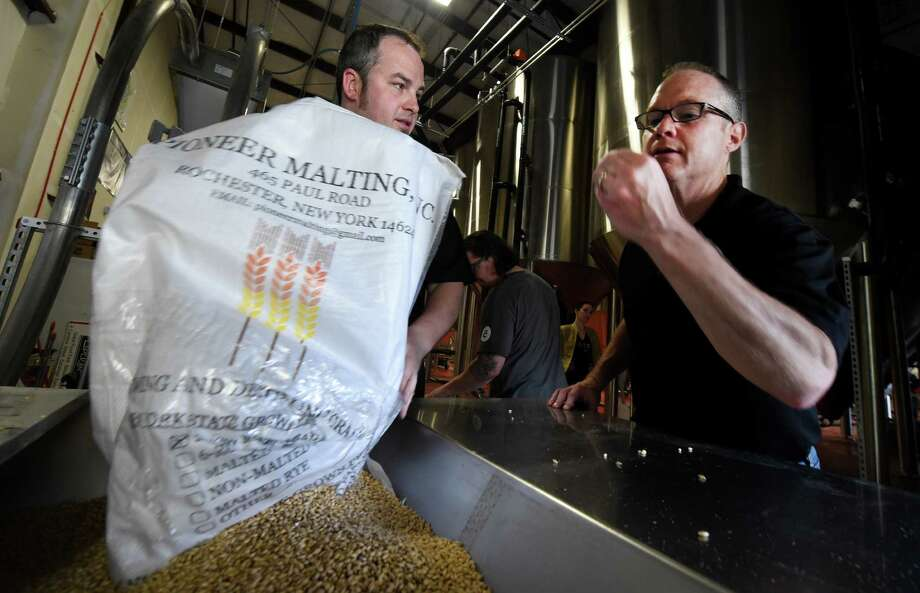 Hutch Kugelman head brewer for Crossroads Brewery of Athens, N.Y., left lends a hand with a load of grain  Wednesday May 27, 2015 at the Schmaltz Brewing Company during the first annual New York Statewide Collaboration Brew Day in Clifton Park, N.Y.  Inspecting the grain is Paul Leone, executive director of the NYS Brewers Association.    (Skip Dickstein/Times Union) Photo: SKIP DICKSTEIN / 00032023A