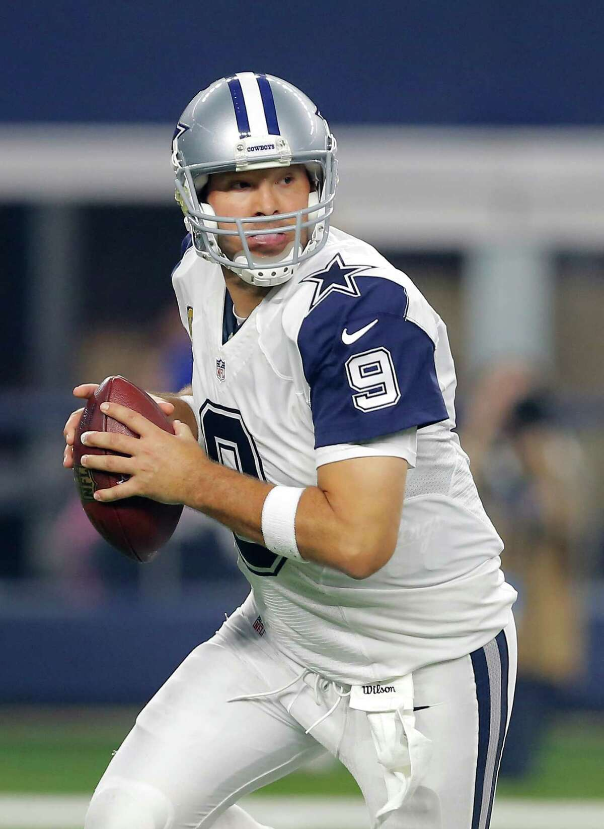 Dallas Cowboys' Tony Romo rolls out of the pocket before passing against the Carolina Panthers on Nov. 26, 2015, in Arlington.