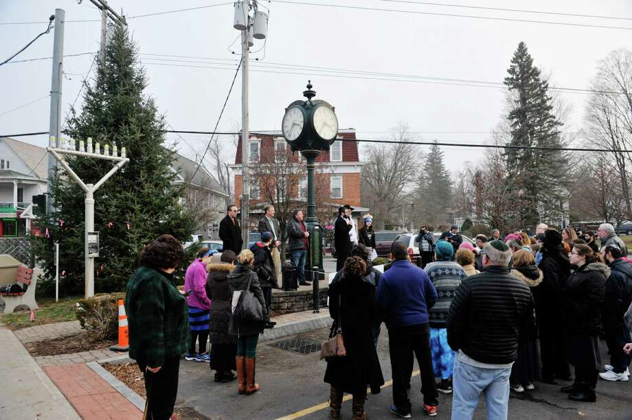 People gather at the clock tower at the Four Corners in Delmar for a First night of Chanukah Bethlehem Chabad Menorah Lighting on Sunday, Dec. 6, 2015, in Delmar, N.Y.  The event was put on by the Chabad House of Delmar.  (Paul Buckowski / Times Union) Photo: PAUL BUCKOWSKI / 10034537A