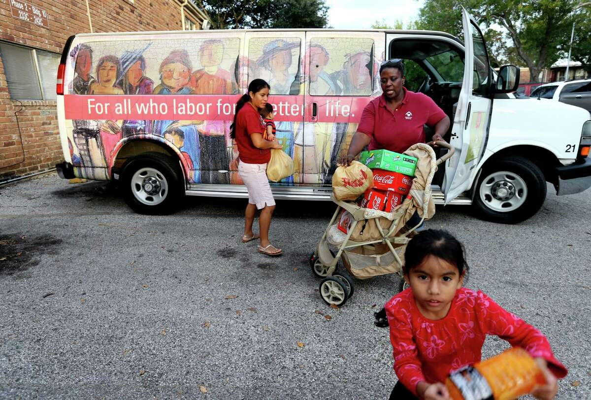 Driver Karen Hicks helps Aura Velasco unload groceries from the Magic Bus, a service that operates in Gulfton, where nearly half of residents have a household income under $25,000.