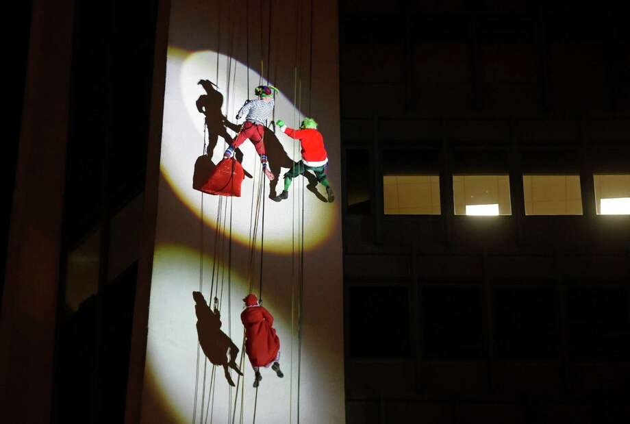 """New York Yankees General Manager Brian Cashman, top left, dressed as """"Cash the Elf,"""" battles the Grinch, played by Jason Teitelbaum, as Mrs. Claus, played by Yogi Berra's granddaughter Lindsay Berra, looks on while rappelling down the side of the 22-story Landmark Square during the 2015 Heights and Lights event in Stamford on Sunday evening. For more photos of the holiday event, see page A3 or go to www.stamfordadvocate.com Photo: Tyler Sizemore / Hearst Connecticut Media / Greenwich Time"""