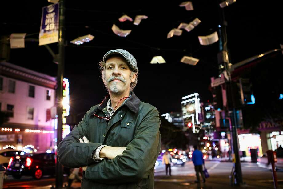 "Artist Brian Goggin stands in front of his installation ""Language of the Birds,"" which hangs at the intersection of Broadway and Columbus Avenue. Photo: Gabrielle Lurie, Special To The Chronicle"