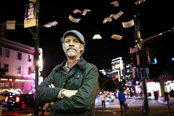 "Artist Brian Goggin stands in front of his installation ""Language of the Birds"", which hangs at the intersection of Broadway Street and Columbus Avenue, in San Francisco, California on Thursday, December 3, 2015."
