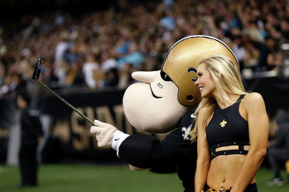 """A New Orleans Saints cheerleader poses with a selfie stick with """"Sir Saint"""" in the first half of an NFL football game against the Carolina Panthers in New Orleans, Sunday, Dec. 6, 2015.(AP Photo/Bill Feig)"""