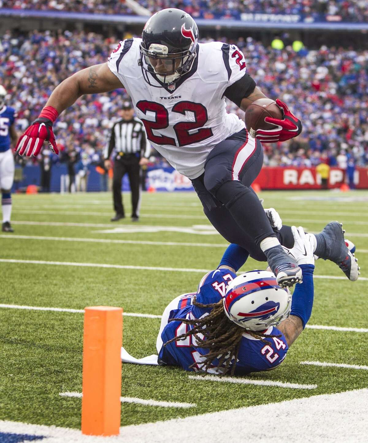Houston Texans running back Chris Polk (22) jumps over Buffalo Bills cornerback Stephon Gilmore (24) for an 11-yard touchdown reception during the second quarter of an NFL football game against the Buffalo Bills at Ralph Wilson Stadium on Sunday, Dec. 6, 2015, in Orchard Park, N.Y. ( Brett Coomer / Houston Chronicle )