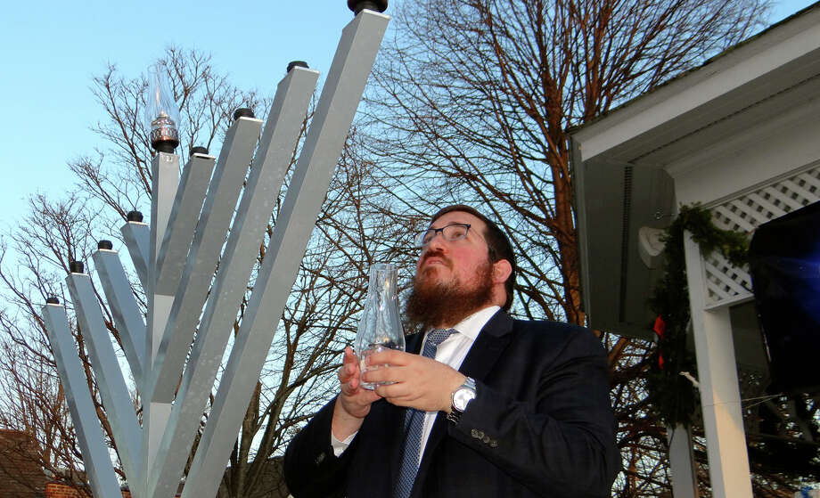 Rabbi Shlame Landa prepares to light the first menorah candle during a community Hanukkah celebration sponsored by Chabad of Fairfield. Photo: Mike Lauterborn / For Hearst Connecticut Media / Fairfield Citizen