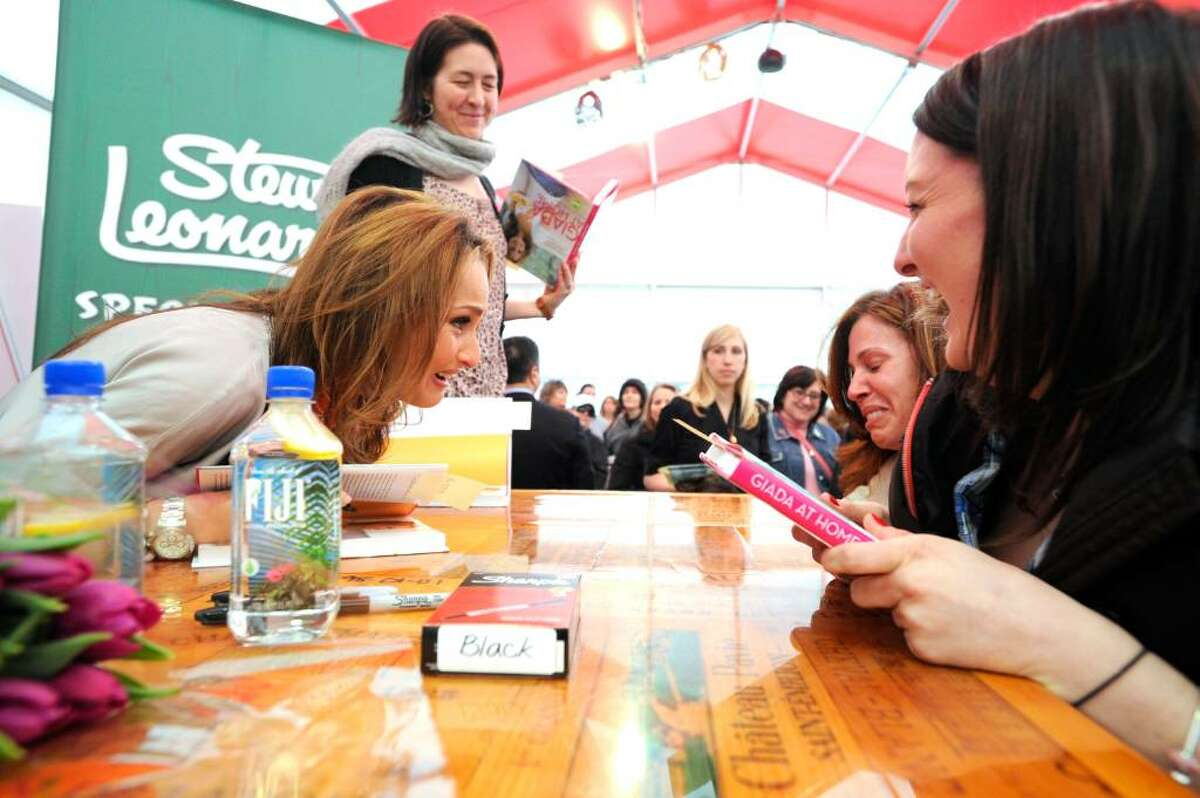 Celebrity chef Giada De Laurentiis greets overwhelmed fan Maria Stepnowsky as Kristin Emerick, right, and Kate Tyler, standing, look on at Stew Leonard's in Norwalk, Conn., Wednesday evening March 31, 2010. De Laurentiis was on hand to sign copies of her new book