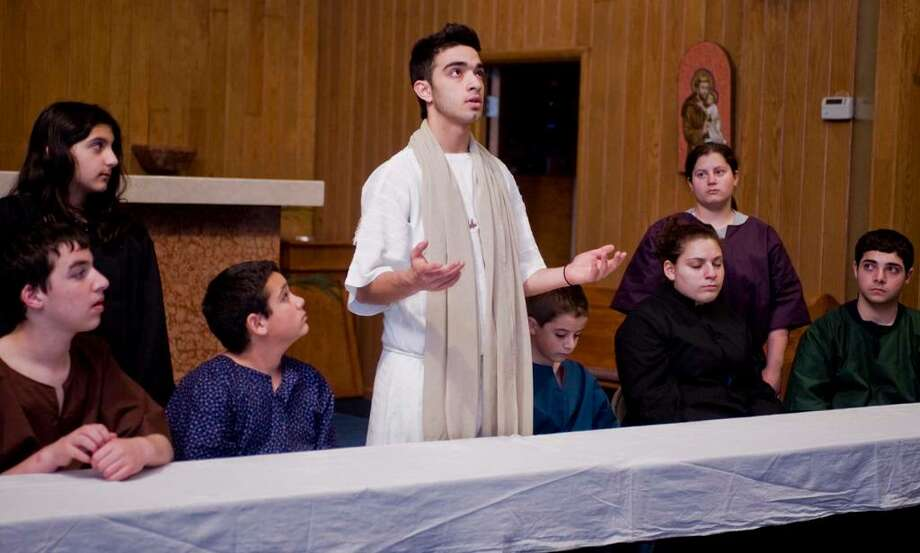 "Soly Zarrini of Brookfield,center, is surrounded by his apostles — from left, Austin Burns, Christina Shoushani and David Stewart of Danbury; Jonathan Sweeney of Brookfield; and Lydia Jabbour, Jaci Jowdy and Gabe Lahoud of Danbury in a recent production of   ""The Passion of Christ"" at St. Anthony Church on Granville Avenue, Danbury. Photo: Scott Mullin / The News-Times Freelance"