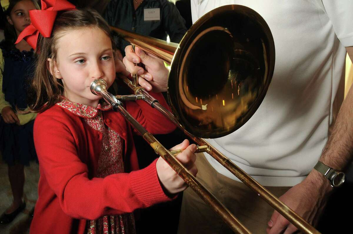 Eugenie Montz,7, gives the trombone a try at the Houston Symphony's Magical Musical Morning