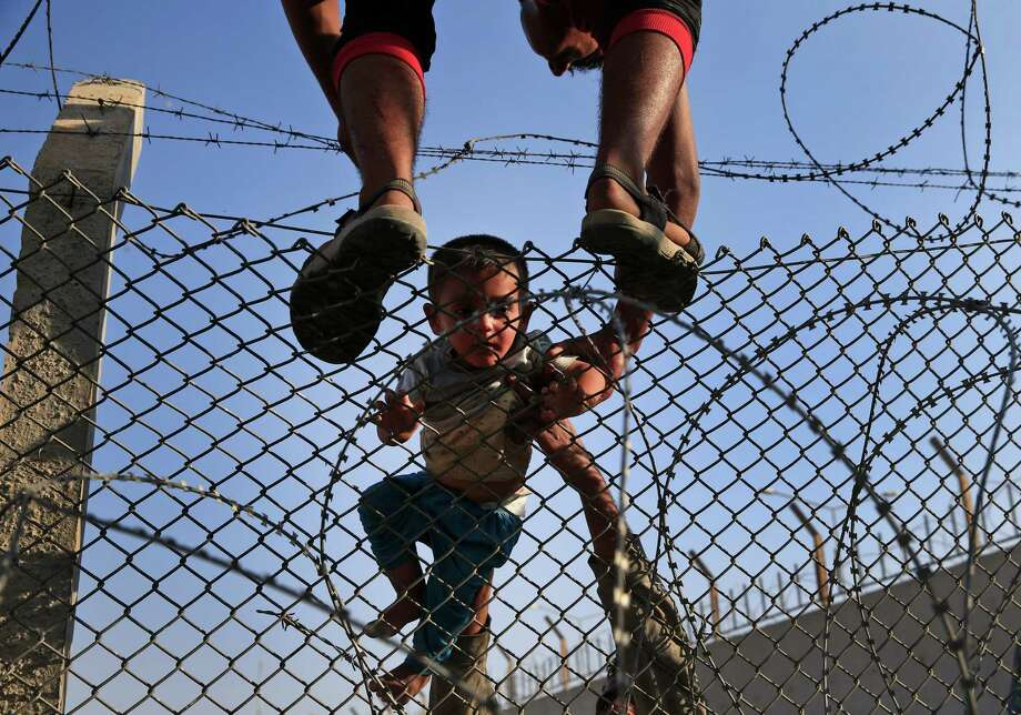 Texas, traditionally a hub for refugees, has been sparring with the Obama administration over the relocation of people fleeing the Syrian civil war. Here are the 10 things you need to know about the legal battle. Syrian refugees carry a baby over the border fence into Turkey from Syria, June 14, 2015. Photo: Lefteris Pitarakis, Associated Press / AP