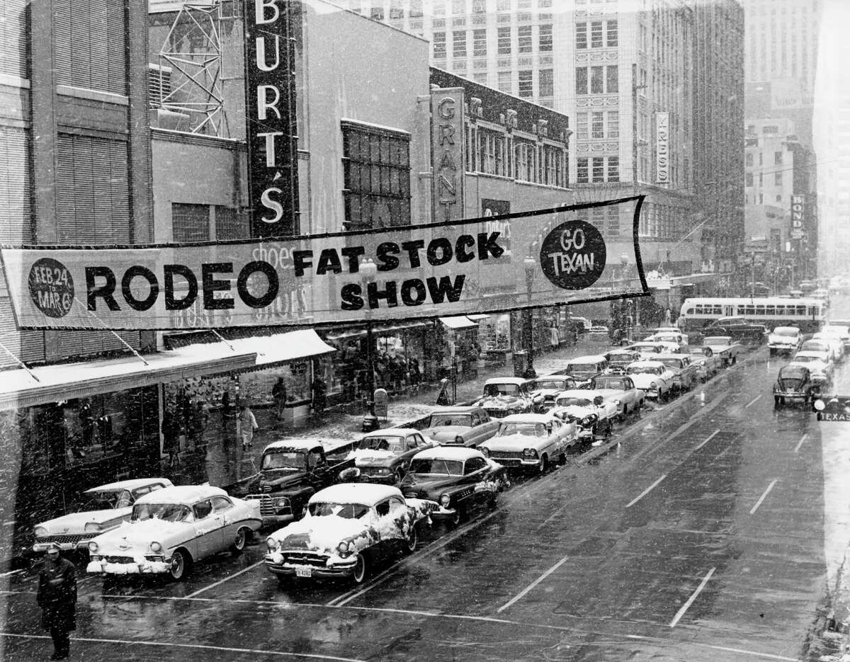Snow falls on traffic at Main St. and Texas Ave. in downtown Houston. February 13, 1960.