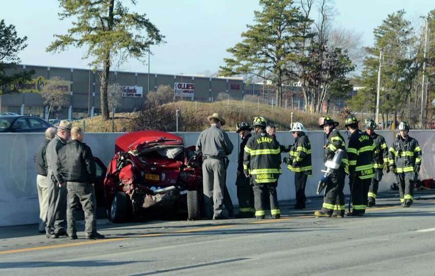 Emergency workers and state police investigate the scene of an auto accident at Exit 24 of the Thruway westbound in the outer lanes where a tractor trailer collided with a car Monday afternoon, Dec. 7, 2015, in Albany, N.Y. (Will Waldron/Times Union)