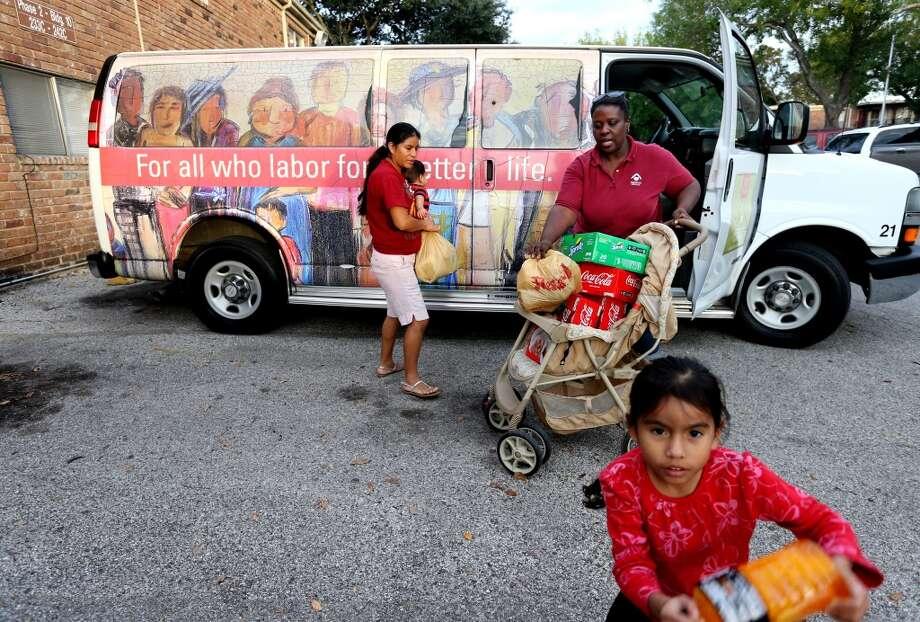 "Driver Karen Hicks helps Aura Velasco to put her purchases in a ""Magic Bus"" in Houston. Photo: Gary Coronado, Houston Chronicle"
