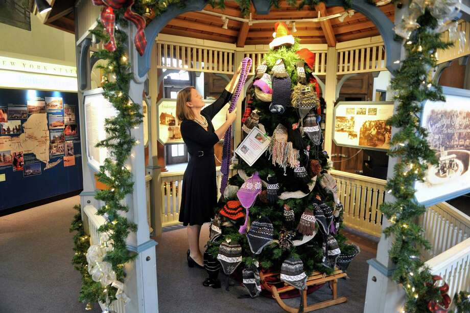 Heather McElhiney, director of Saratoga Heritage Area Visitor Center, hangs a donated scarf on the Mitten Tree at the center on Monday, Dec. 7, 2015, in Saratoga Springs, N.Y.  For over the past ten years the center has been putting up the tree and encouraging people to donate winter hats, gloves, mittens, heavy socks and even long underwear for all ages to help those in need.  Those in need are welcomed to come into the center and take what they need off the tree.  The center will also distribute the items as the tree fills up to the Franklin Community Center, the Shelters of Saratoga and Captain Youth and Family Services.  The visitor center is open Monday through Saturday from 9:00am to 6:00pm and on Sunday from 10:00am to 3:00pm.  (Paul Buckowski / Times Union) Photo: PAUL BUCKOWSKI / 10034522A