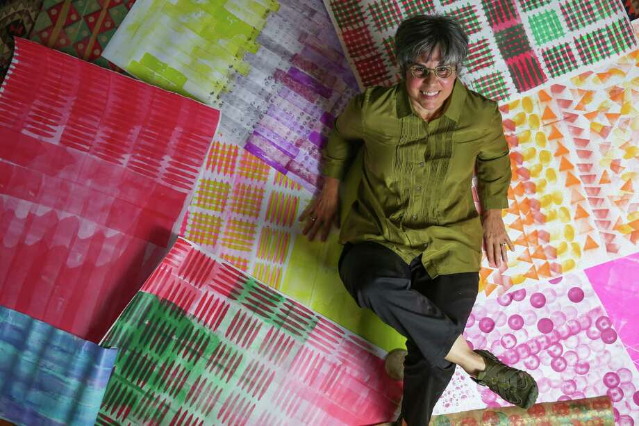 Susan Petty shows off the wrapping paper she made with stamps and paint. Photo: Michael Ciaglo, Staff / © 2015  Houston Chronicle