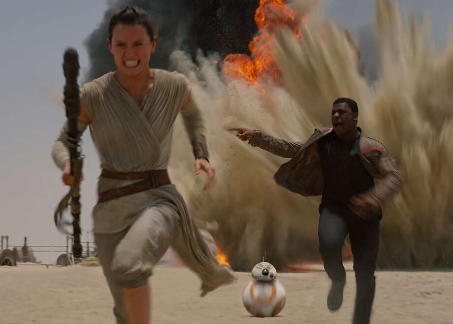 "Rey (Daisy Ridley, left) and Finn (John Boyega) run from a TIE fighter attack in ""Star Wars: The Force Awakens."" Ridley had never handled a weapon before. Photo: Walt Disney Studios Lucasfilms"