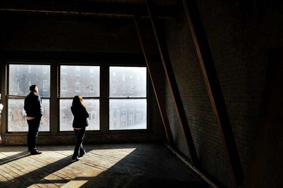 Jeff Buell, left, president and CEO of Sequence Development and Elizabeth Young Jojo, chief operating officer of Sequence Development, stand on one of the upper floors of The Arts Center of the Capital Region during a tour of the space they plan to turn into apartments, on Monday, Dec. 7, 2015, in Troy, N.Y.   (Paul Buckowski / Times Union) Photo: PAUL BUCKOWSKI / 10034536A