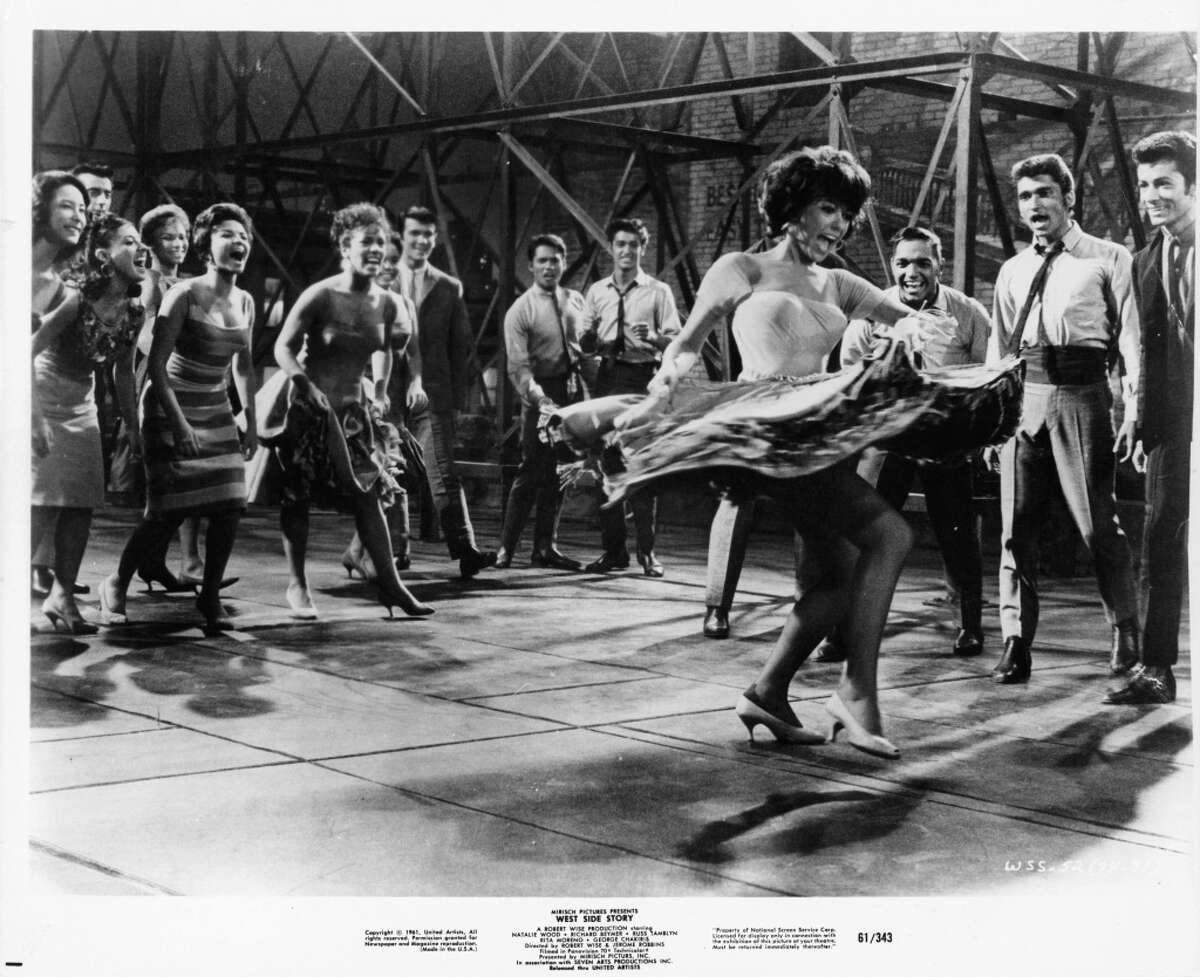 Rita Moreno surrounded by a group of people that are cheering her on while she dances in a scene from the film 'West Side Story', 1961.