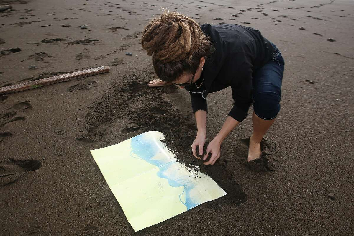 San Francisco photographer Meghann Riepenhoff works on producing abstractions with ocean waves while exposing cyanotype on strathmore bristol paper at Rodeo Beach in Sausalito, California, on Monday, December 7, 2015. Reipenhoff has a solo exhibition called